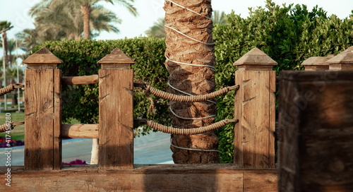 Fototapeta premium Wooden handrails with intertwined rope close up.