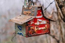 Birdhouse Made With Various Old License Plates Hanging From A Tree.