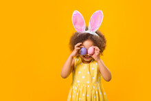 An African Girl With Rabbit Ears On Her Head With Painted Eggs In Her Hands On A Yellow Background.