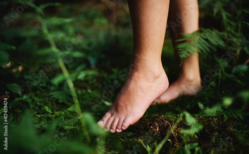 Fotografie, Obraz Bare feet of woman standing barefoot outdoors in nature, grounding concept