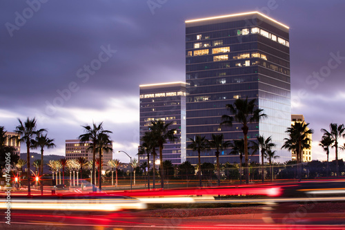 Photo Twilight evening view of traffic streaming by the downtown skyline of Irvine, California, USA