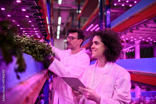 Canvas Print Workers using tablet on aquaponic farm, sustainable business and artificial lighting