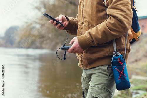 Obraz Tourist holds a portable charger with a smartphone in his hand. A man on the background of a lake with a backpack charges the telephone with Power Bank. Concept on the theme of tourism. - fototapety do salonu