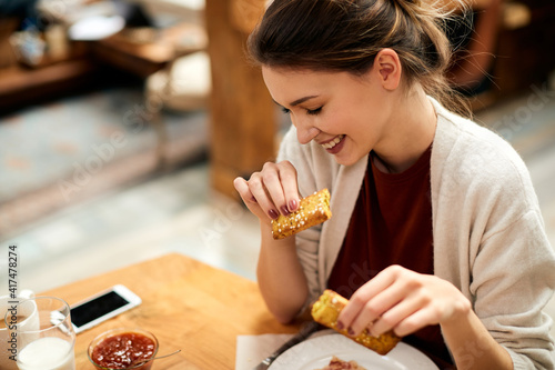 Obraz Young smiling woman enjoying in breakfast at home. - fototapety do salonu