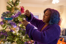 Black Woman Decorating Christmas Tree At Home, Comfortable In Robe