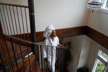 Woman Walking Up Spiral Staircase In Bathrobe