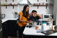 Indian Mom And Son Cooking And Baking In The Kitchen