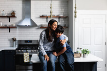 Indian Mother And Son Embracing On Kitchen Counter, Family Loving Moment