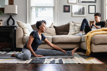 Black Mom Stretches In Family Room, Teenage Son On Phone In Background, Fitness, Health And Wellness