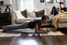 Black Mom Working Out In Family Room, Teenage Son On Phone In Background, Planks