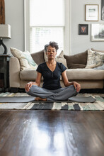 Black Mom Meditates In Family Room, Teenage Son On Phone In Background, Peaceful Health  And Wellness