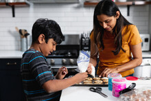 Indian Mother And Son Decorating Fresh Baked Cookies In The Kitchen