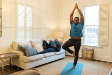 Man Watches His Partner Doing Yoga, Tree Pose