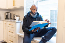Black Man, Cozy, Reading Book In Nook At Home