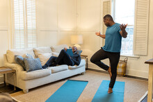 Man Encourages Partner On Couch While He Does Yoga At Home, Fitness