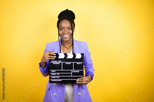 Fototapeta Young african american business woman holding clapperboard very happy having fun