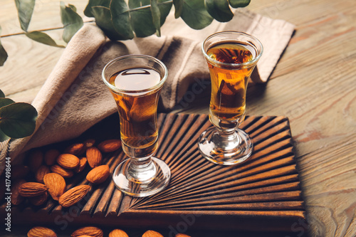 Fototapeta Glasses of almond liquor and nuts on wooden background obraz