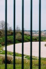 Vertical closeup shot of metal bars on a gate near a trail