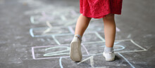 Closeup Of Little Girl's Legs And Hop Scotch Drawn On Asphalt. Child Playing Hopscotch Game On Playground Outdoors On A Sunny Day.