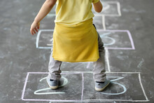 Little Boy's Jump On Hop Scotch Drawn On Asphalt. Child Playing Hopscotch Game On Playground Outdoors On A Sunny Day.