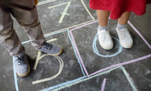 Closeup Of Little Boy And Girl Legs And Hop Scotch Drawn On Asphalt. Child Playing Hopscotch Game On Playground Outdoors On A Sunny Day. Kids Having Fun. Best Friends