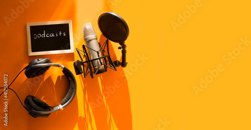 Obraz na płótnie Professional microphone with waveform and headphones on yellow background banner