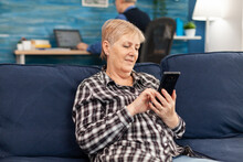 Hapy Elderly Lady Texting On Phone Relaxing On Sofa Enjoying Retirement Lifestyle. Senior Woman Browsing On Internet Using Smartphone Sitting On Sofa In Home Living Room.