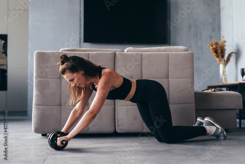 Fotografia, Obraz Fit woman working out with ab exercise wheel at home.