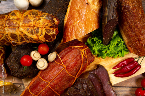 Assortment of cold cuts, a variety of processed cold meat products. On a wooden background © YERMAKAVETS