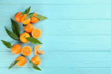 Fresh Ripe Tangerines With Leaves On Light Blue Wooden Table, Flat Lay. Space For Text