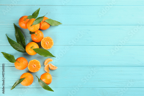 Tablou Canvas Fresh ripe tangerines with leaves on light blue wooden table, flat lay