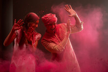 A HAPPY YOUNG WOMAN AND MAN RAISING HANDS TO SHIELD THEMSELVES FROM COLOURS BEING THROWN AT