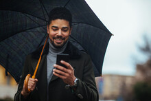 African American Male Using Phone On A Rainy Day