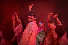 A GROUP OF YOUNG MEN AND WOMEN HAPPILY DANCNG TOGETHER WHILE CELEBRATING HOLI