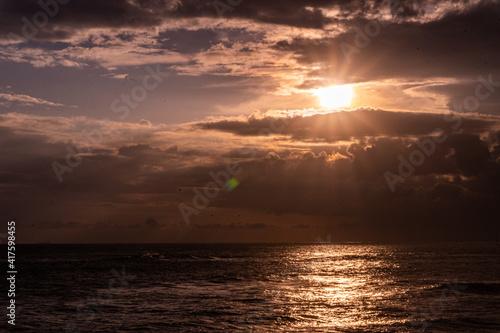 Obraz Zachód słońca nad oceanem i skalistym wybrzeżem. - fototapety do salonu