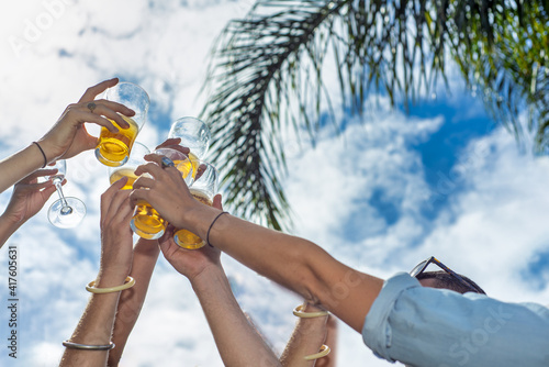 People, men, women, leisure, friendship and celebration concept - happy friends drinking beer and clinking glasses at bar or pub © jovannig