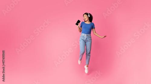 Fotografie, Obraz Happy asian woman singing using smartphone as mic