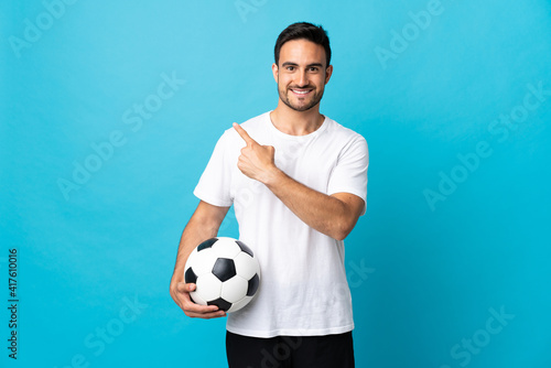 Fototapeta Young handsome man isolated on blue background with soccer ball and pointing to the lateral obraz