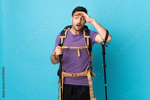 Fototapeta Young caucasian man with backpack and trekking poles isolated on blue background doing surprise gesture while looking to the side obraz