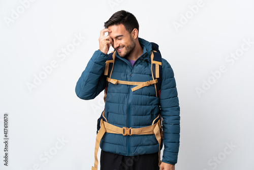 Fototapeta Young mountaineer man with a big backpack isolated on white background laughing obraz