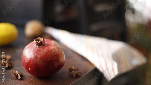 Fototapeta Granat owoc czerwony na stole drewnianym ciemnym obraz