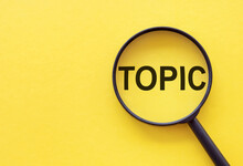 The Word TOPIC Is Written On A Magnifying Glass On A Yellow Background.