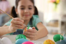 Little Girl Painting Easter Eggs At Table Indoors, Focus On Hands