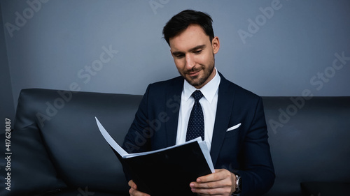 Businessman holding paper folder in hotel room - fototapety na wymiar