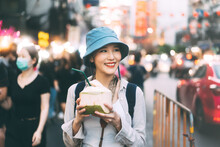 Young Adult Asian Foodie Woman Backpack Traveller Eating Coconut Juice At China Town Street Food.