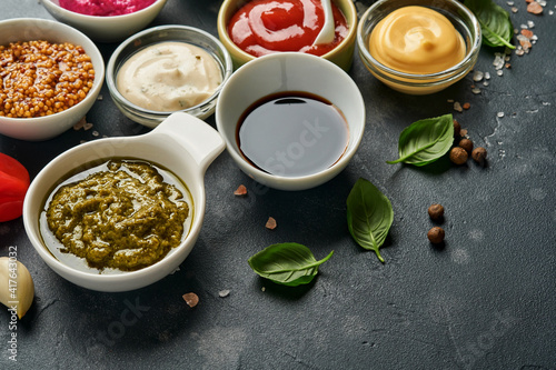 Fototapeta Set of sauces in bowls - ketchup, mayonnaise, mustard, soy sauce, bbq sauce, pesto, chimichurri, mustard grains on dark stone background