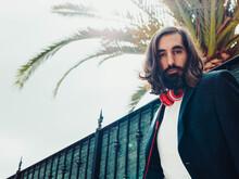 Hombre Elegante Y Rico Con Cascos Auriculares Debajo De Una Palmera