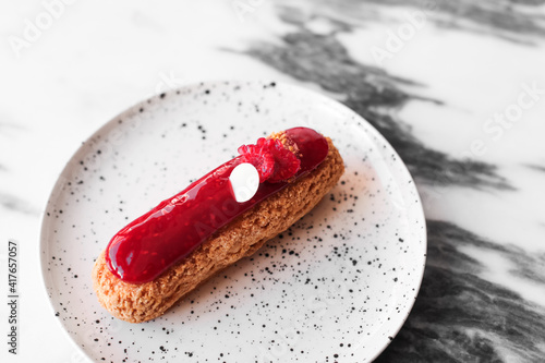 Carta da parati An eclair with berries, pink jam, white chocolate on a white table, marble table