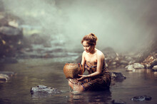 Woman Sitting In A River Bathing, Thailand
