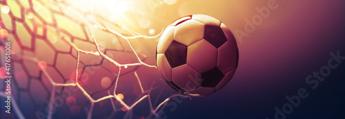 Fotografia Soccer ball in the net in the sunbeams. Golden background